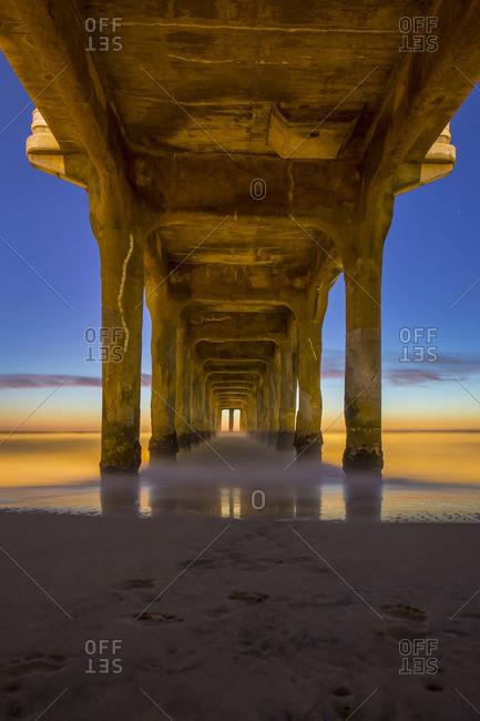 Underside of Manhattan Beach pier at sunset