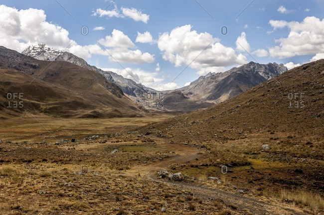Dirt path in a valley and distant mountains in the Cordillera Blanca, Peru