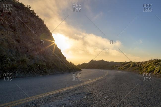 Sun setting over a highway on San Bruno Mountain, California
