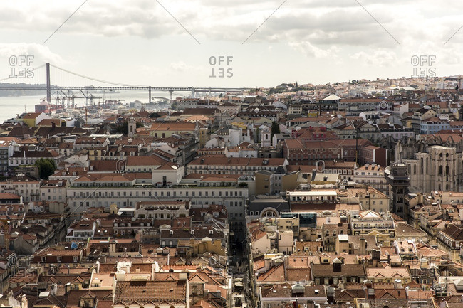 Lisbon, Portugal - June 23, 2015: Cityscape of rooftops and distant suspension bridge