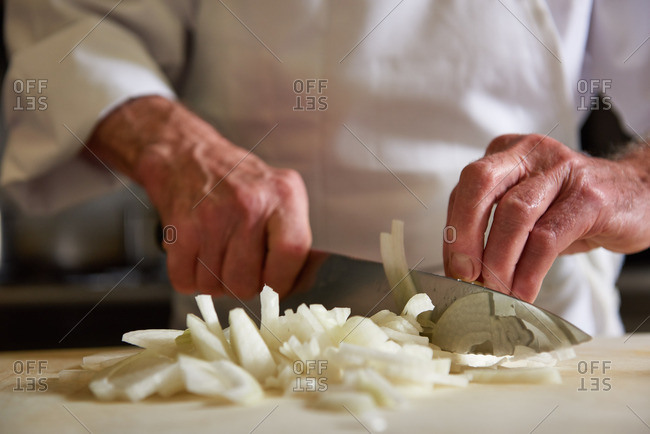 Chef cutting onions with a large French knife in the kitchen of a traditional French restaurant in Incline Village, Lake Tahoe, Nevada.