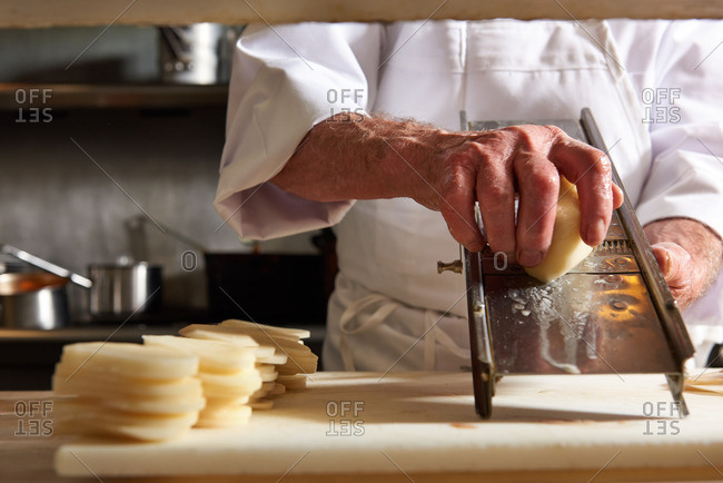 Traditional French Chef slicing potatoes on a vintage mandolin in a French kitchen in Incline Village, Lake Tahoe, Nevada.