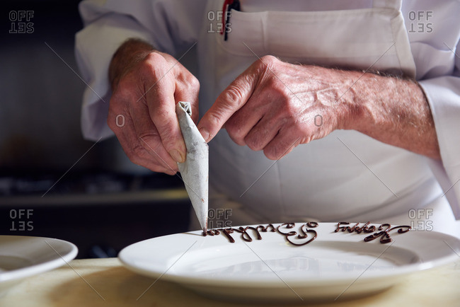 Traditional French Chef writing Happy Birthday in chocolate frosting on a white plate in a traditional French restaurant in Incline Village, Lake Tahoe, Nevada.