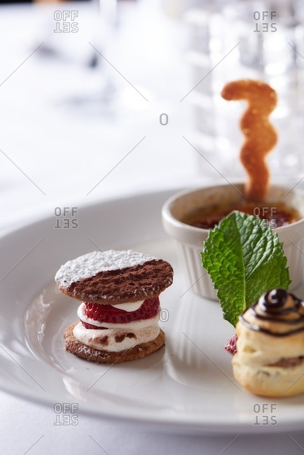 Four small dessert bites consisting of an apricot tart, mini cream puff, black and white cookie and mini creme brulee served on a single plate in a traditional French restaurant in Incline Village in Lake Tahoe, California.