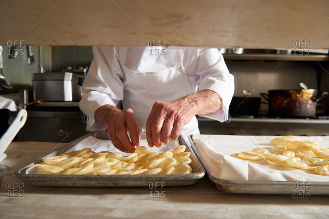 Traditional French Chef preparing Pommes De Terre Souffles in a French restaurant kitchen photographed in natural light in Incline Village, Nevada, Lake Tahoe.