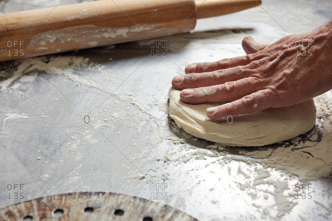 Raw Pizza Dough being worked and rolled out on a floured aluminum surface.