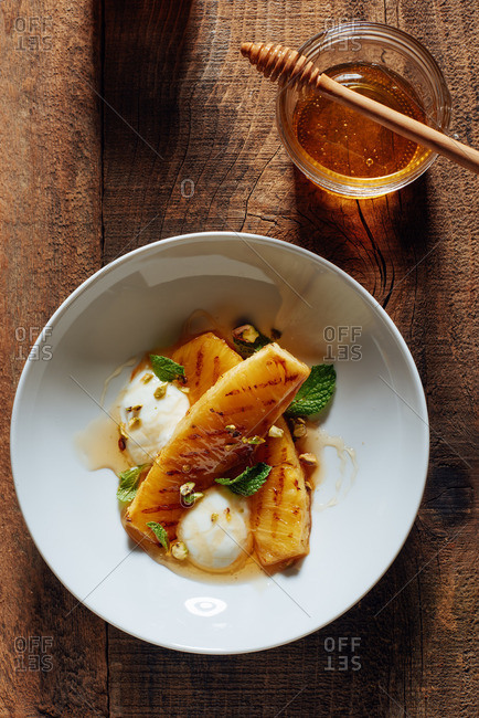 A healthy gluten free dessert of grilled pineapple, yogurt, honey, mint leaves and pistachio on a rustic wooden table.