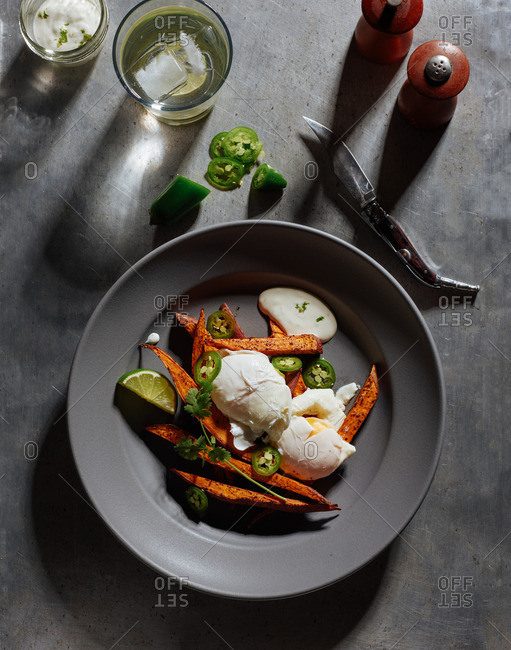 Brunch of ancho chile sweet potato fries, poached eggs and lime creme served with cilantro and fresh sliced jalapenos