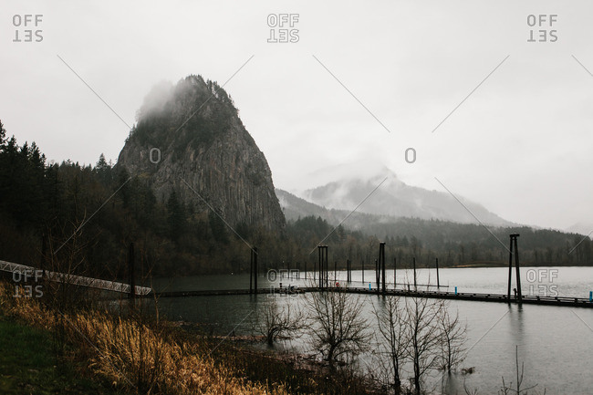 Large Mountains covered in fog behind a lake on a gloomy day