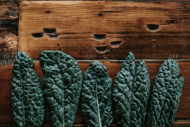 Fresh leaves of kale sitting on a wood table