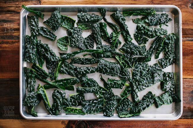 Kale chips being prepared on a baking sheet