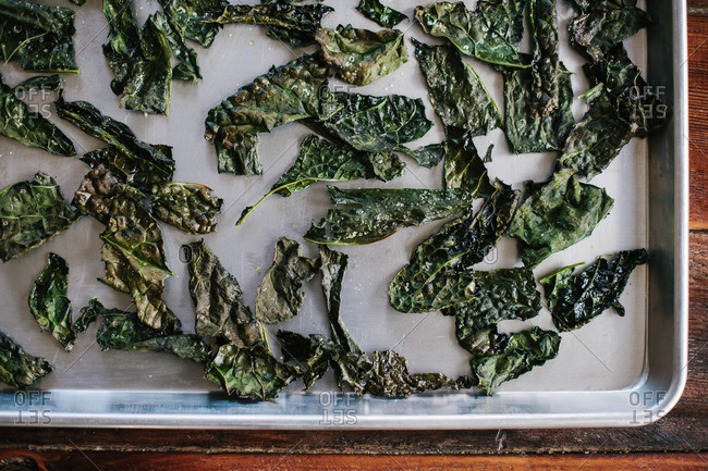 Cooked kale chips on a baking sheet