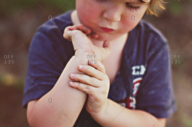 Boy holding his arm and showing his owie