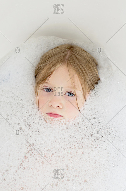 Girl in a bubble bath with face surrounded by bubbles