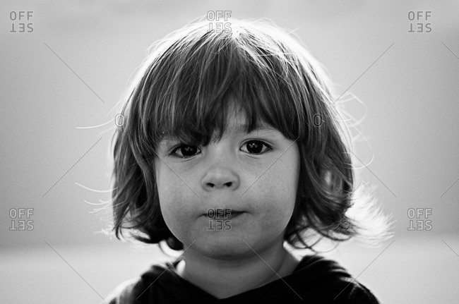 Portrait of a boy with long hair looking into the camera