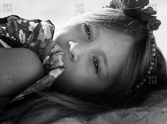 Portrait of a girl lying on beach in frilly dress