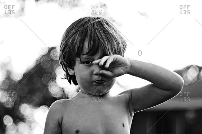 Black and white portrait of a boy rubbing his eye