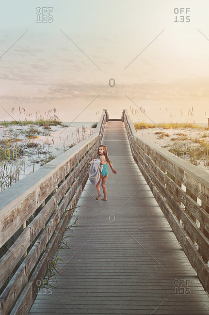 Girl walking down a boardwalk to the beach