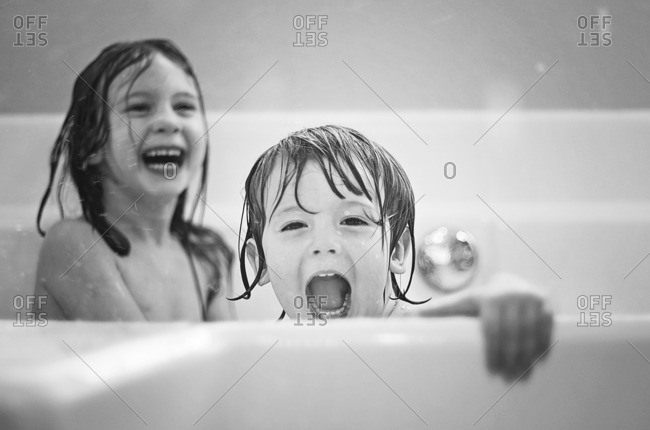 Two siblings playing together at bath time
