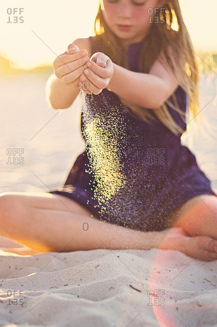 Girl playing with sand at the beach