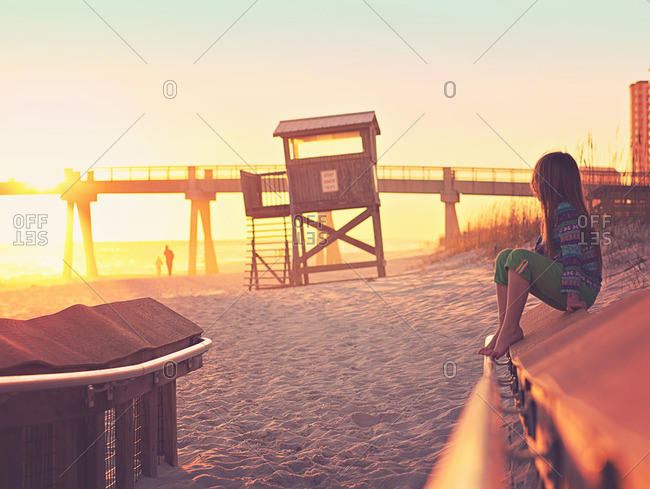Girl sitting on railing on a sandy beach near sunset