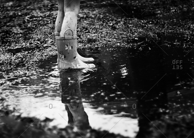 Girl in rain boots standing in a puddle