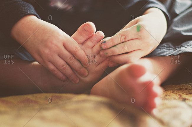 Child touching feet with sandy toes