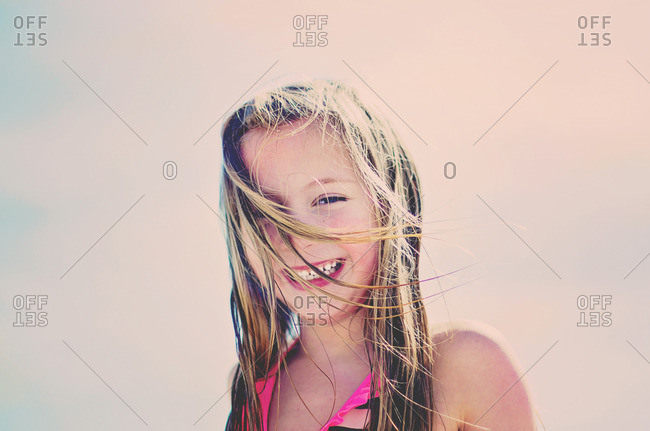 Smiling girl in the wind at the beach