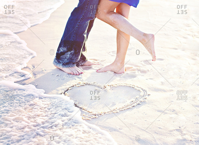 Couple at the beach with a heart in the sand