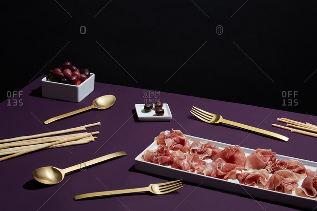 Prosciutto and olives served with breadsticks