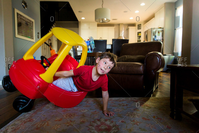 Boy tipping over toy car in living room
