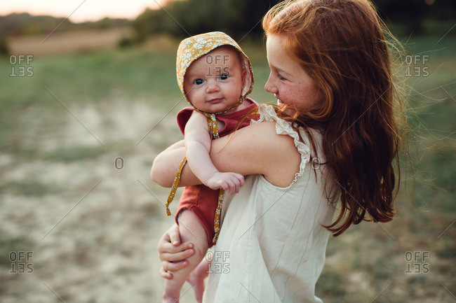 Girl holding her baby sister in her arms at sunset