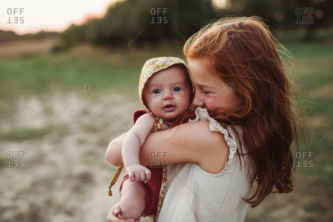 Girl cuddling her baby sister outdoors at sunset