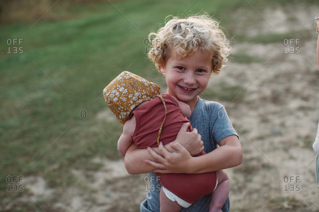 Little boy carrying his baby sister in a field at sunset