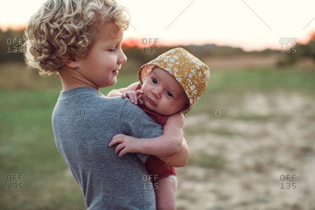 Little boy holding his baby sister in a field at sunset