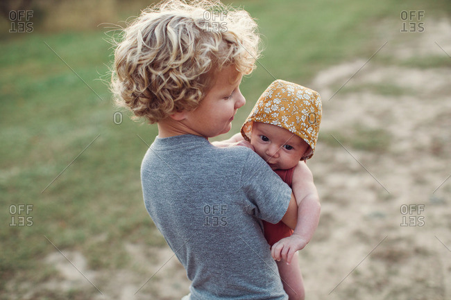 Boy holding his infant sister in a rural field at sunset