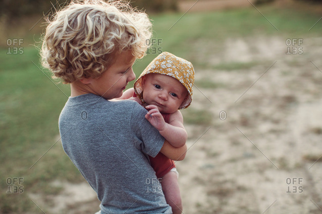 Boy carrying his infant sister in a field at sunset
