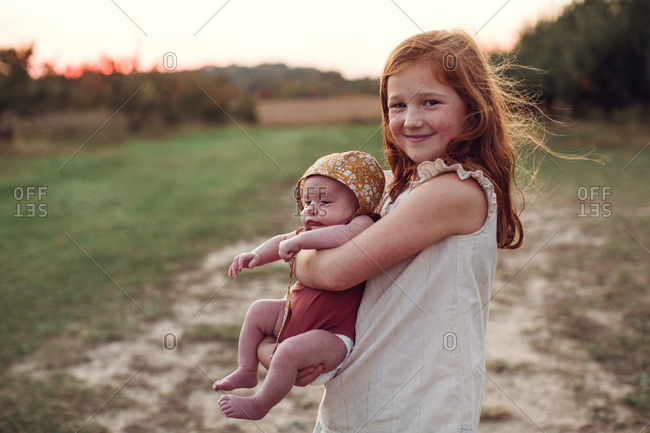 Girl holding her baby sister and smiling in a field
