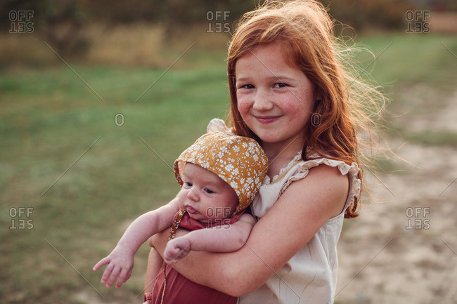 Girl holding her baby sister and smiling in a field at sunset