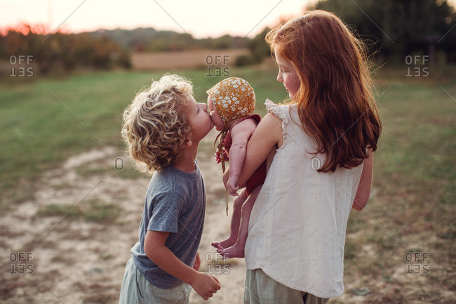Girl holding her baby sister while her brother kisses her cheek