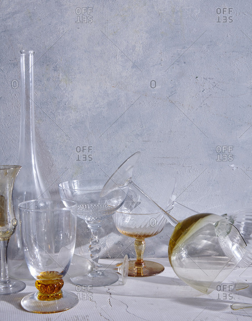 Still life of variety of glasses with some knocked over