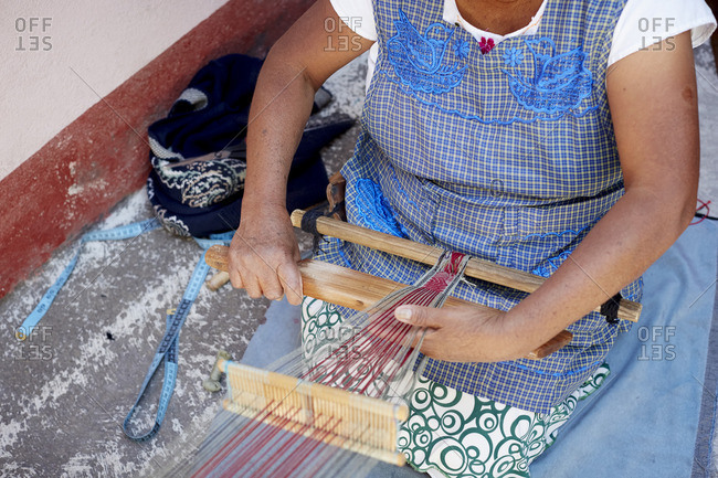 Mexican woman weaving outside on hand loom