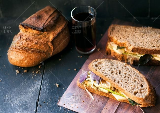 Loaf of homemade bread and sandwich with cheese and veggies