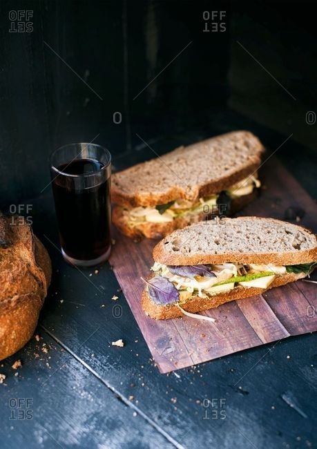 Sandwich with veggies and cheese and a loaf of homemade bread