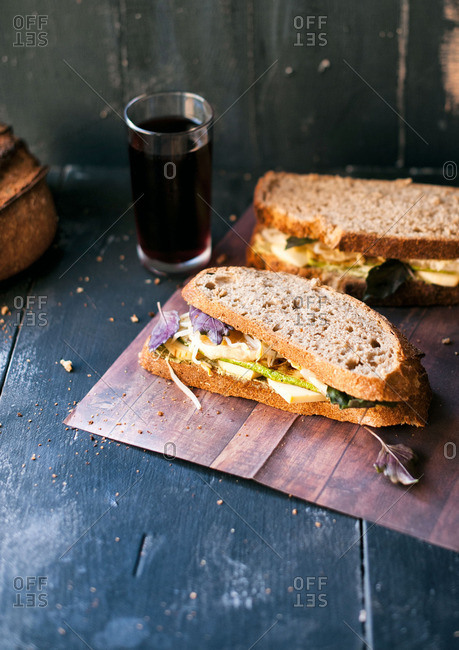 Sandwich with veggies and cheese and a dark beverage
