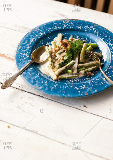 Plate of asparagus, dill and walnuts in a cream sauce