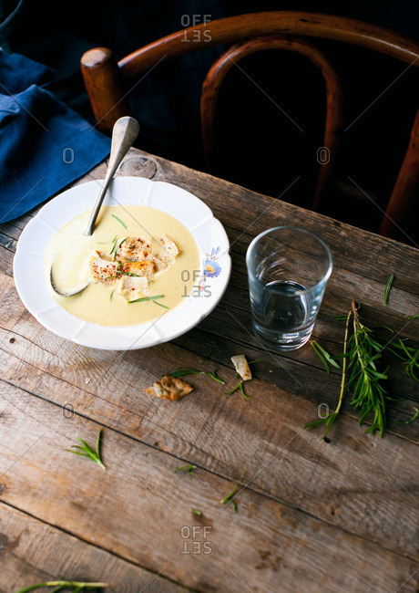 Creamy soup with fresh rosemary and crackers on a rustic table