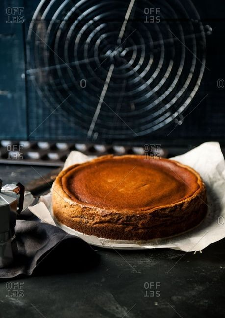 Golden cake on parchment paper in front of a vintage fan