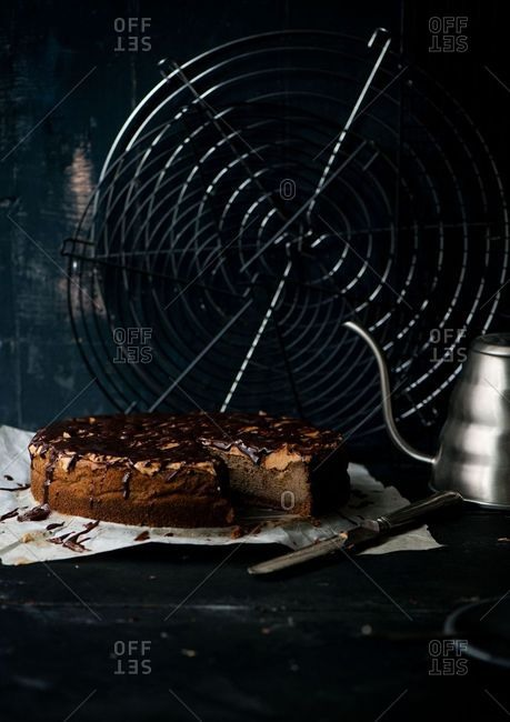 Cake with frosting and chocolate sauce in front of a retro fan