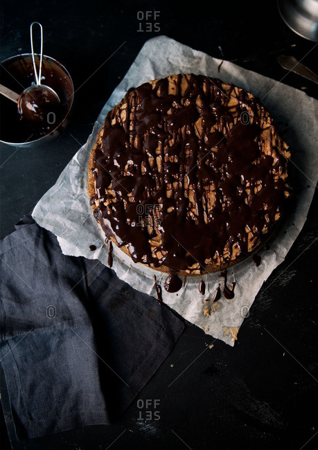 Round cake drizzled with chocolate sauce on parchment paper